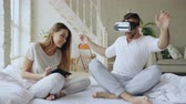 play video game : Young cute couple with tablet computer and virtual reality headset playing 360 VR video game while sitting in bed at home