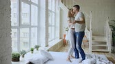 closeness : Young beautiful and loving couple dancing and kissing on bed in the morning at home Stock Footage
