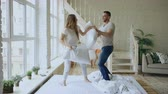 женат : Young happy and loving couple having pillow fight and kissing on bed at home