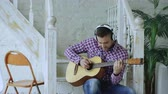 acústico : Happy attractive man sitting on stairs with wireless headphones study playing acoustic guitar at home Vídeos
