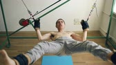 push : Young man doing exircise on quartering crossfit equipment and pull his arms and legs with ropes
