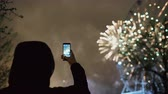fişekçilik : Closeup silhouette of man watching and photographing fireworks explode on smartphone camera outdoors