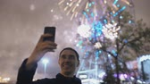 fajerwerki : Closeup of young cheerful man watching and making selfie picture with fireworks on smartphone camera outdoors