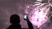 fişekçilik : Slowmotion of closeup silhouette of man watching and photographing fireworks explode on smartphone camera outdoors