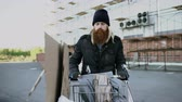 bem estar : Dolly shot of bearded homeless man walking down the street with shooping card at cold autumn day Stock Footage