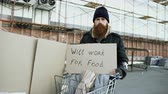 pobreza : Portrait of young homeless man with cardboard looking at camera and wants to work for food standing near shopping cart