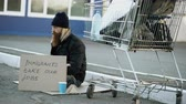 pobreza : Bearded young homeless man with cardboard sitting near shopping cart and drink alcohol at cold day. Immigrants crisis in Europe