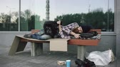 полиция : Young Homeless man trying to sleep under jacket on bench at the sidewalk