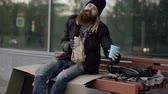 abuse : Very drunk homeless man talking to people walking near him and beg for money and show hand sign while sitting on bench at the sidewalk Stock Footage
