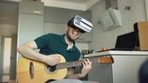 acústico : Happy young man sitting at kitchen learning to play guitar using VR 360 headset and feels him guitarist at concert at home
