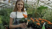 horticultura : Portrait of Cheerful young woman garden worker in apron smiling and holding flower in hands in greenhouse