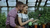 florista : Happy young florist family in apron working in greenhouse. Attractive man embrace and kiss his wife while she watering flowers with garden spray Vídeos