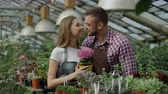 zahradník : Happy young florist couple in apron smiling in greenhouse. Attractive man embrace and kiss his wife holding flower and smile together into camera