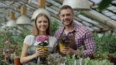 florista : Happy young couple smiling in greenhouse. Attractive woman and man florists in apron work in garden looking into camera