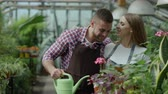 local de trabalho : Happy young gardener couple in apron working in greenhouse. Cheerful man embrace and kiss wife while she talking phone