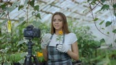 zahradník : Young smiling woman florist in apron talking and recording video blog for her online vlog about gardening