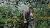 zahradník : Happy young florist family in apron have fun during working in greenhouse. Attractive man embrace and kiss his wife