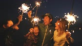 sunset : Group of young friends having a beach party. Friends dancing and celebrating with sparklers in twilight sunset