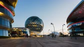 bloco : ASTANA, Kazakhstan - June 10, 2017: Timelapse of modern sphere building of EXPO with people moving around on sunset
