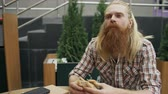 de bom gosto : Bearded student man eating burger in street cafe outdoors