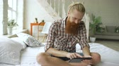 přenosný : Young bearded man using tablet computer sitting on bed in bedroom at home
