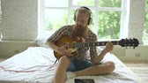 string : Attractive bearded man sitting on bed learning to play guitar using tablet computer in modern bedroom at home
