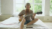 string : Attractive bearded man in headphones sitting on bed learning to play guitar using tablet computer in modern bedroom