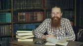campus : Tilt up of Portrait young bearded man smiling happy in library and looking into camera