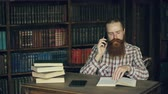 literatura : Young bearded student talking phone while preparing for exams in univercity library