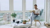 varanda : Young man read book sitting on balcony in modern apartment Stock Footage