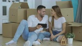 aluguel : Young happy couple sitting on floor using tablet computer to find transport service for reloction in their new home