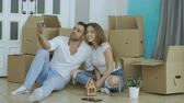 captura : Happy couple sitting on floor in new house. Young man give keys to his girlfriend and kissing her