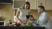 свадьба : Attractive couple chatting in the kitchen early morning. Handsome man using tablet while his girlfriend cooking