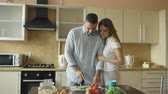 свадьба : Happy young couple in the kitchen. Handsome man meet and feed his girlfriend early morning