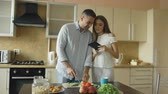 atender : Attractive couple meet in the kitchen early morning. Handsome woman using tablet sharing his husband social media