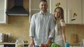 память : Portrait of loving couple smiling ang looking into camera in the kitchen at home