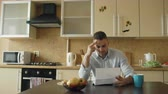 печаль : Uspet young man reading letter with unpaid bill in the kitchen at home Стоковые видеозаписи