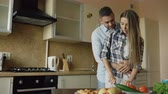 свадьба : Happy young couple in the kitchen. Attractive cooking woman feeding her boyfriend in the morning