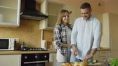 beijos : Young woman covering boyfriends eyes with hands and surprising him in the kitchen at home