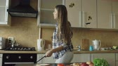 tancerze : Cheerful young funny woman dancing and singing while cooking breakfast in the kitchen early morning