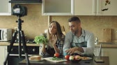 известный : Young attractive couple bloggers shooting video food blog about cooking on dslr camera in the kitchen