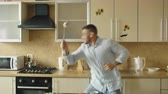 łyżka : Handsome man having fun in the kitchen fencing with ladle and spoon while cooking breakfast at home