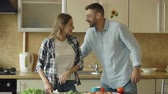 женат : Happy young couple in the kitchen. Attractive woman cooking breakfast and cuff her boyfriend who want to taste food Стоковые видеозаписи