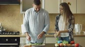 огурцы : Happy young couple cooking breakfast together in the kitchen eartly morning