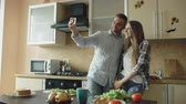 женат : Young happy couple having online video chat in the kitchen at home Стоковые видеозаписи