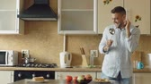 сумасшедший : Slow motion of Attractive young funny man dancing and singing with ladle while cooking in the kitchen at home