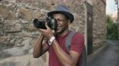 рюкзак : African happy tourist taking photo on his dslr camera. Young man travelling in Europe