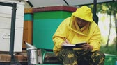 rolnik : Young beekeeper man write in notepad checking harvest while sitting near beehives