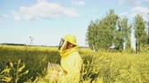 cera de abelha : Pan shot of beekeeper man with wooden frame walking in blossom field while working in apiary Vídeos