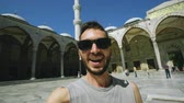 excursão : Handheld of Happy tourist man having online video chat using his smartphone camera near famous blue mosque in Istanbul